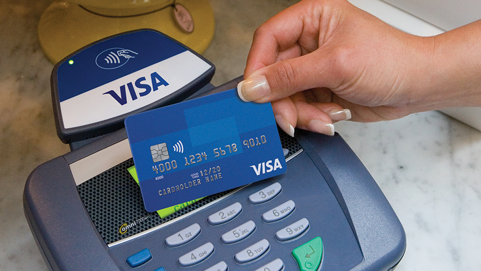 A hand holding a Visa card over a contactless POS system.