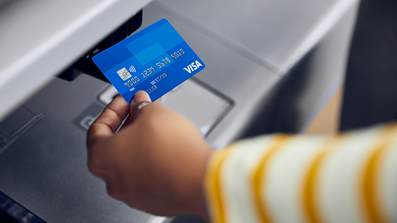 A hand tapping a Visa card with Visa's contactless payments system.